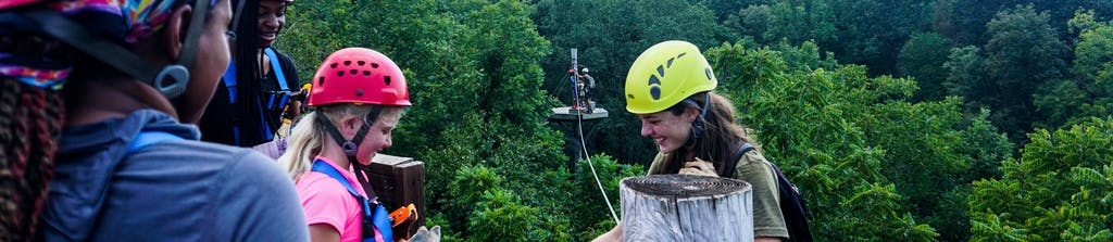 Woman smiling as she guides zipliners high above the trees at Canaan Zipline Canopy Tours near Charlotte, NC