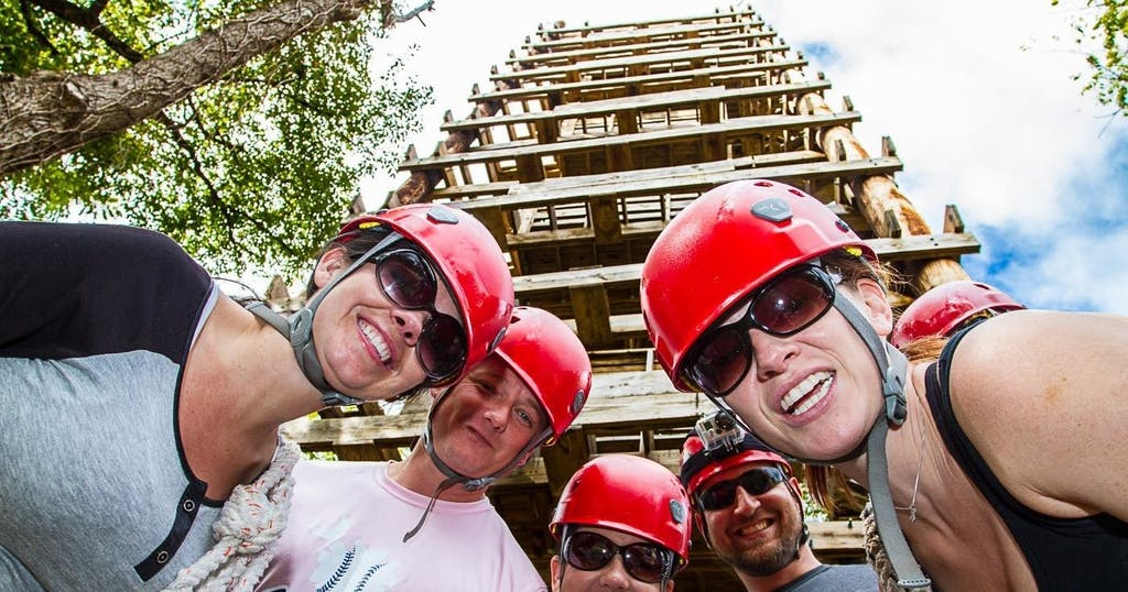 group of zipliners standing in front of a tower and ready to get started