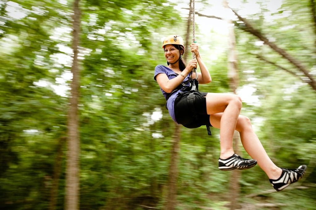 Woman wearing shorts while zipping at Canaan Zipline Canopy Tour