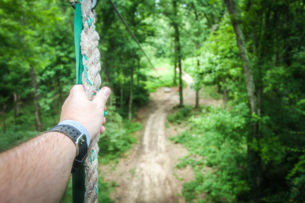 hand holding a zip line rope in the trees
