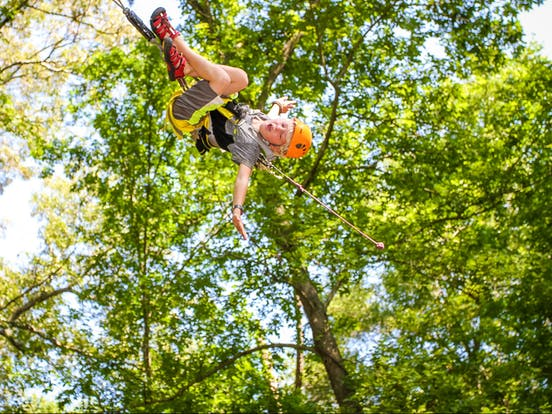 kid hanging upside down ziplining
