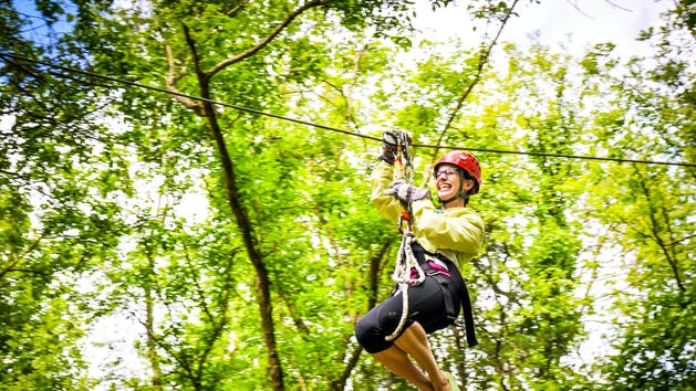 Woman gliding across a zipline at Canaan Zipline Canopy Tours in South Carolina