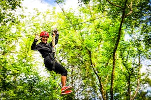 Woman ziplining over the river and through the woods at Canaan Zipline Canopy Tour near Charlotte, NC