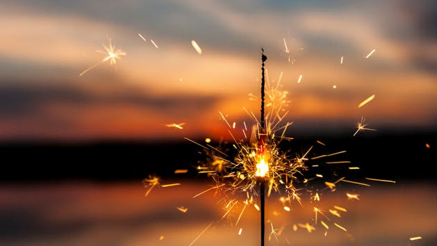 sparkler in the foreground, sunset in the background