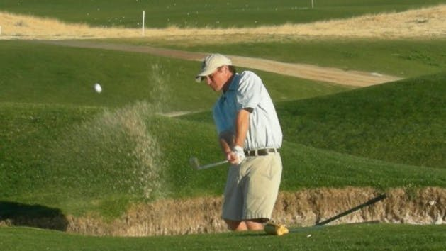 man hitting ball out of sand trap