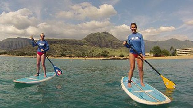 two girls paddle boarding