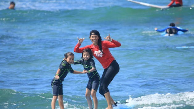 2 kids and instructor surfing