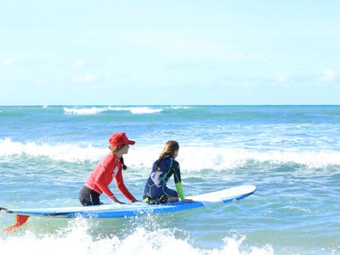 instructor walking with child and surfboard