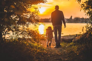 Father and daughter walk into the sunset