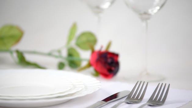 Cutlery and plates on a white background glasses of wine and red rose