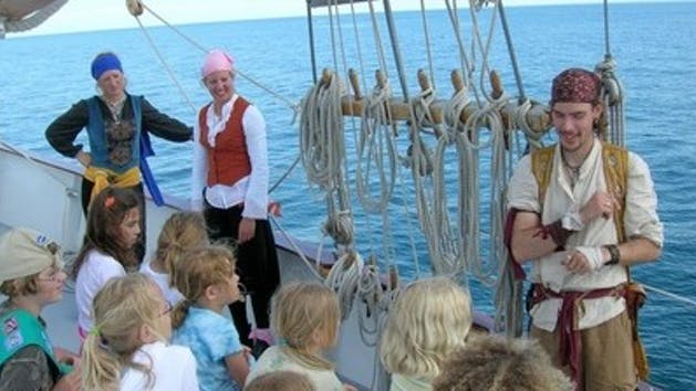 A pirate instructing young kids on the history of Tall Ship WIndy