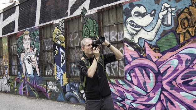 Man Photographing Graffiti in Toronto Alley