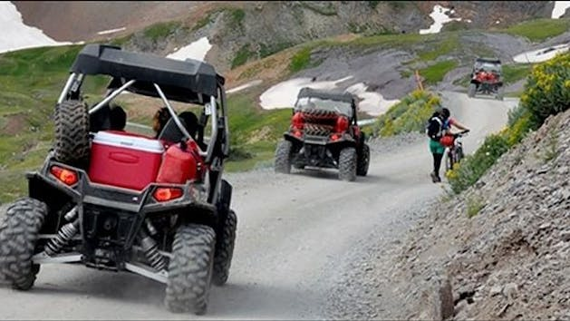 ATVs going on a tour on a dirt road.