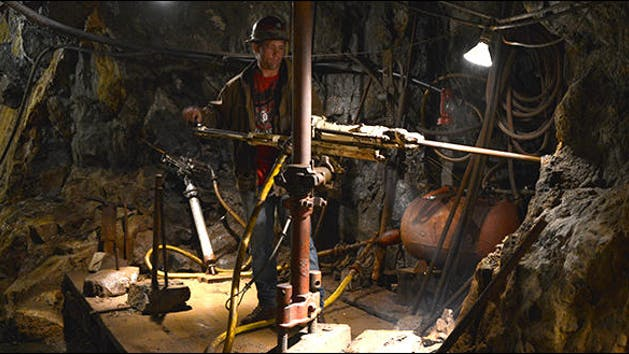 Man operating old mining equipment.