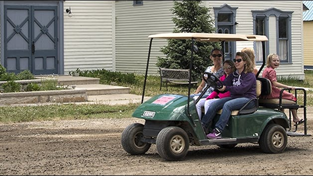 Group of people riding in a golf cart.