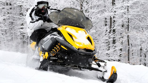a man riding a snowmobile down a snow covered slope