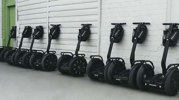 Segways lined up against a white wall