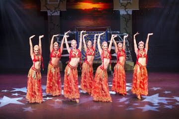 Women on stage dressed in Indian bellydancer costumes with hands upraised