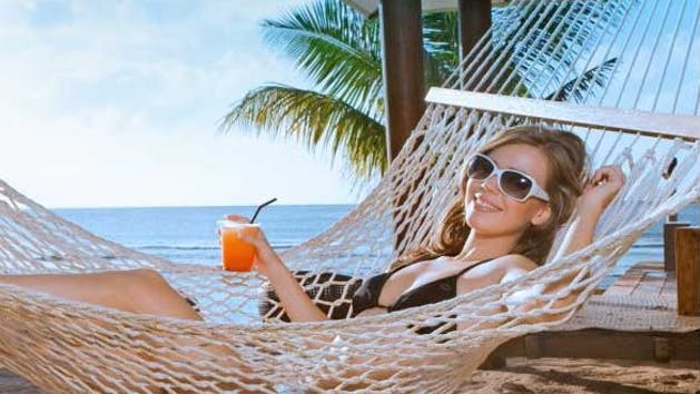 A girl lounging in a hammock with a cocktail in hand on the beach in Tumon, Guam