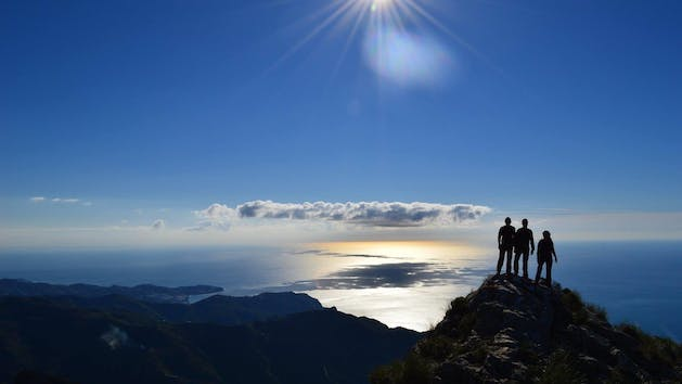 People on top of mountain with sun
