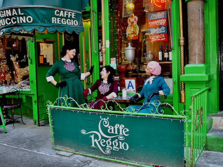 three women laughing in front of a cafe