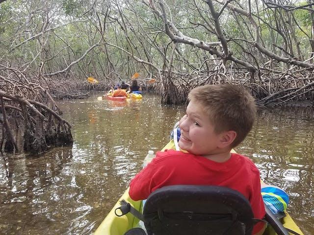 A kid on the mangrove tunnel kayak tour