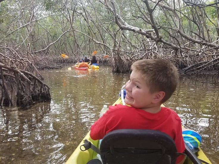 A kid on the mangrove tunnel kayak tour