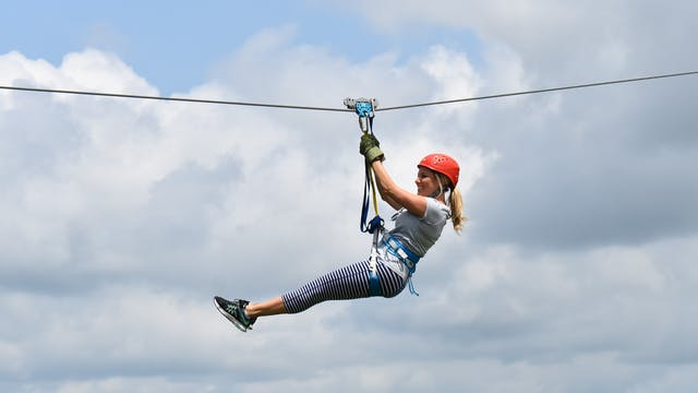 Girl with clouds behind her ziplining