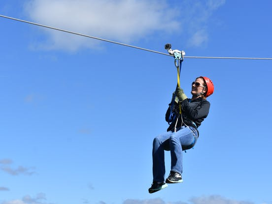 Girl ziplining with the sky in the background