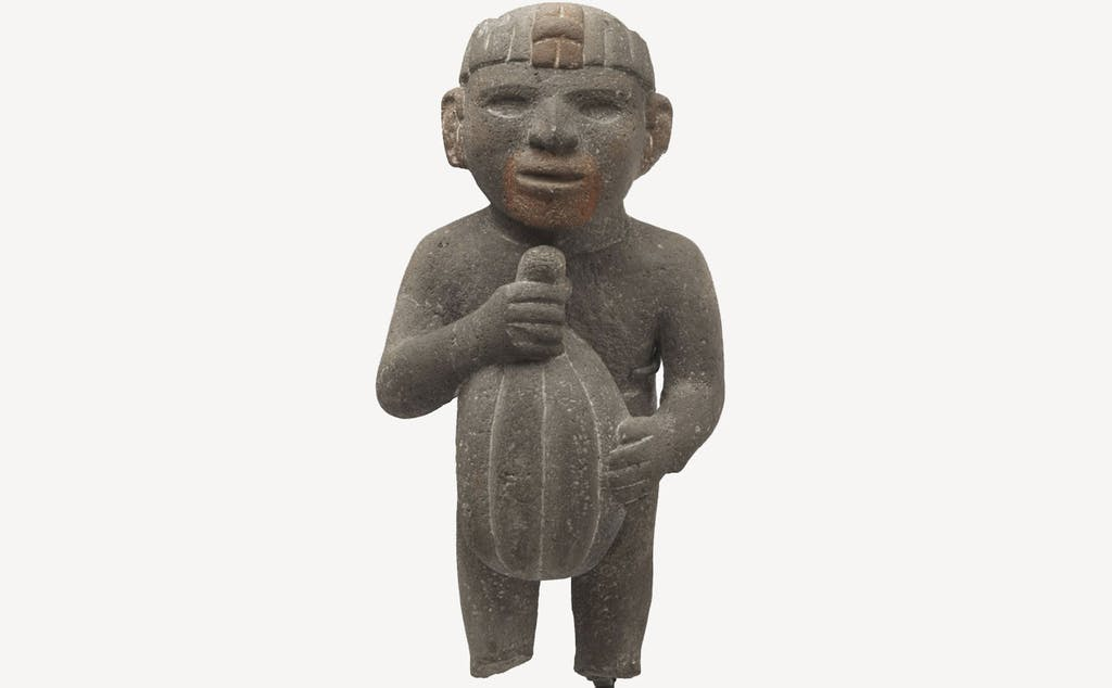 Aztec sculpture depicting a man carrying a cacao pod