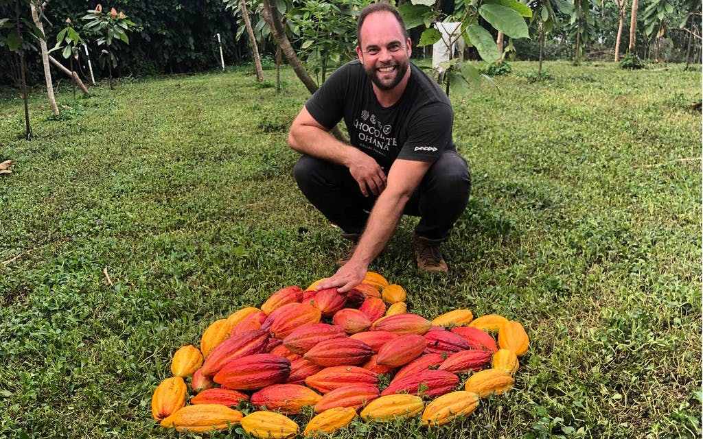 Will Lydgate sits behind cacao pods arranged in a heart shape on the ground.