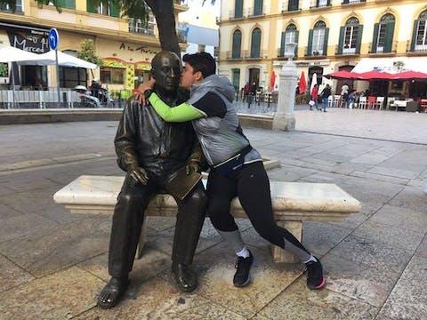 Man kissing statue
