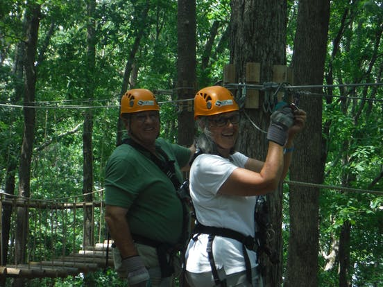 Man and woman on ziplining obstacle course
