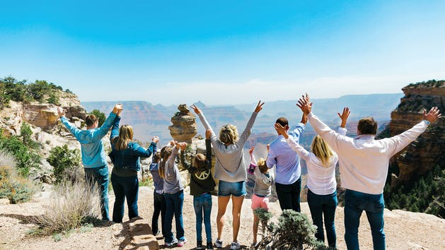 A tour group with their hands in their air