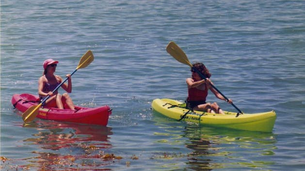 2 women on a pink and a green kayak on the water