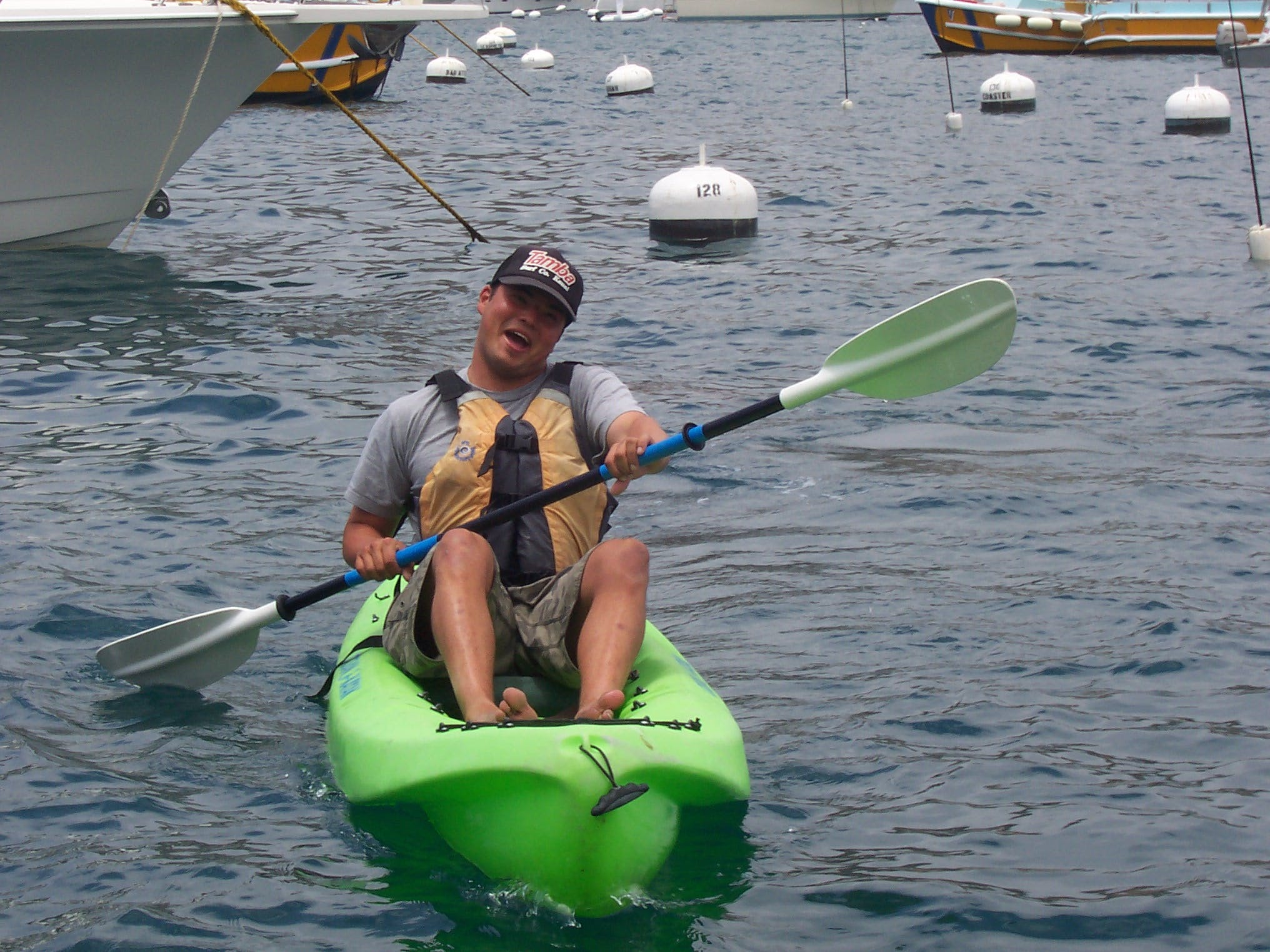 Happy man on a green kayak in the water