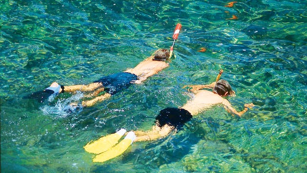 2 boys snorkeling in the water