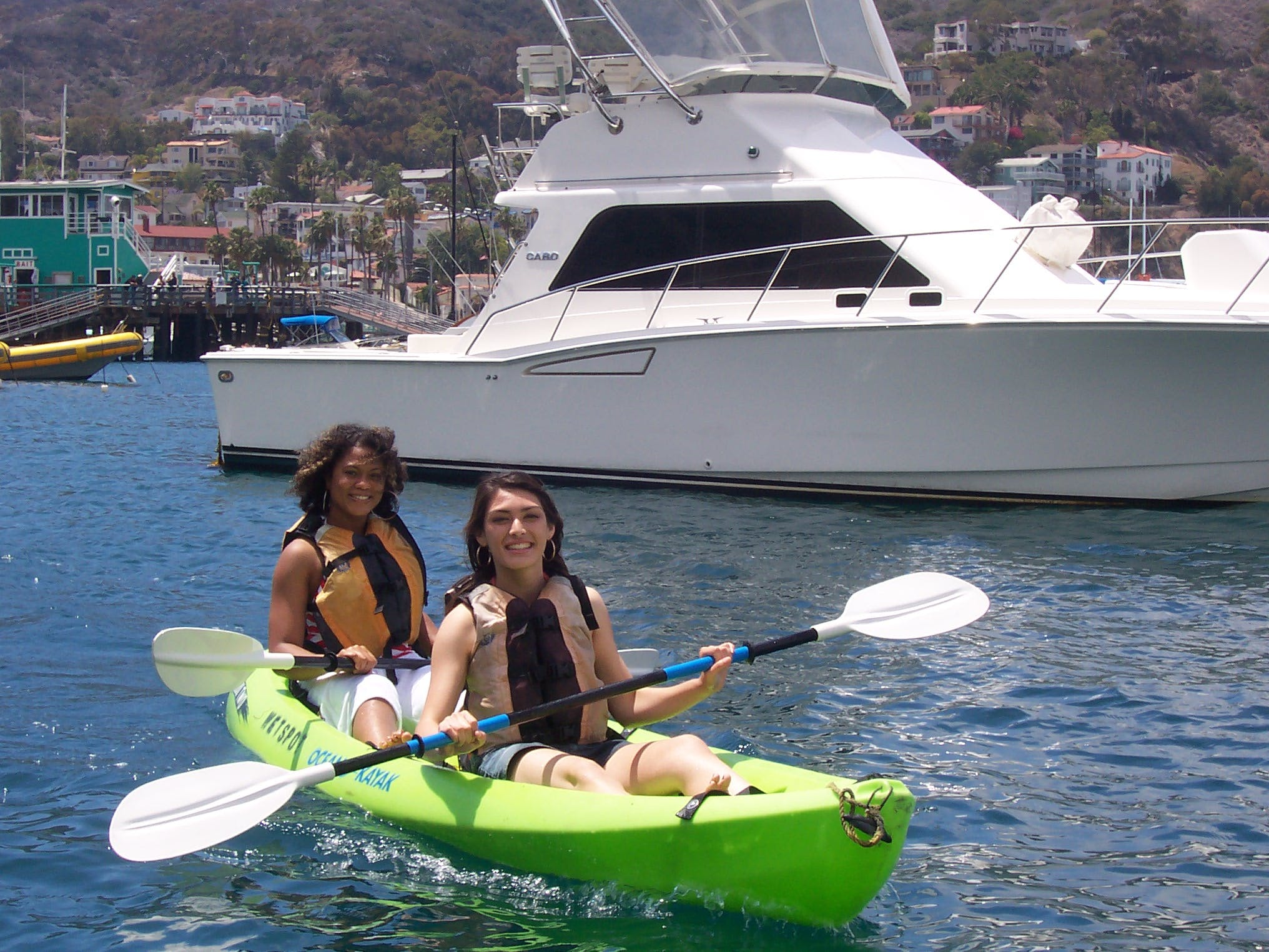 2 Women sharing a tandem green kayak in the water with a boat in the background