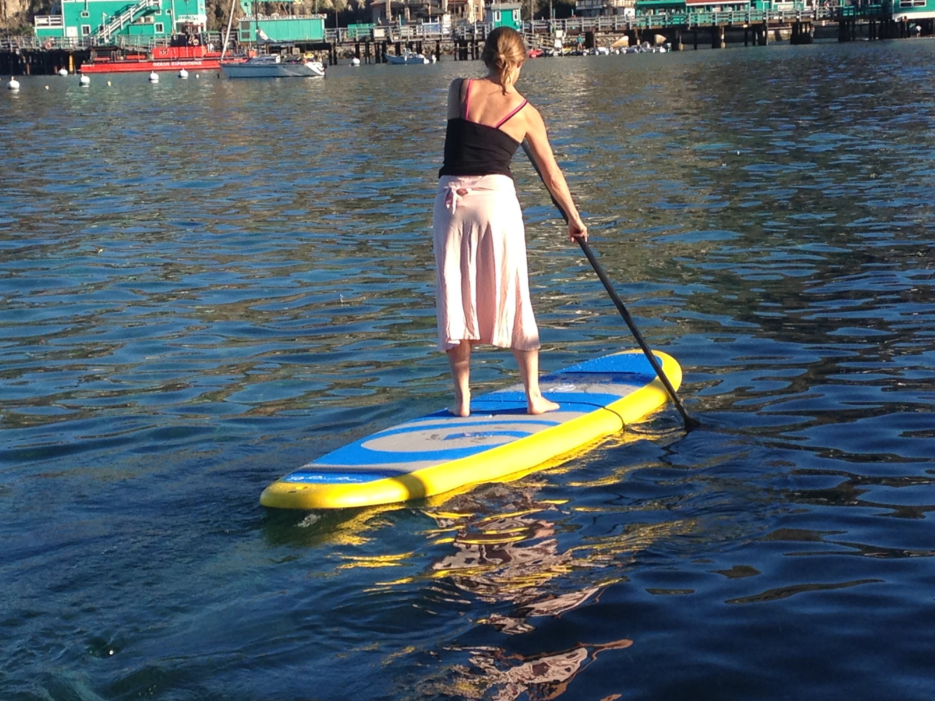 Women standing up on a blue and green stand-up paddle board in the water