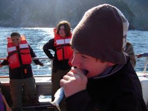 Child eats herring on boat