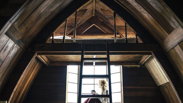 A woman sitting in a cabin looking out at the Alaskan Wilderness