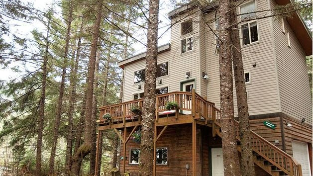 An Alaskan-style home, the two-bedroom Treefort features a natural wood interior, and picture windows that make you feel you're a part of the rainforest. A unique spiral stairway made from a single tree leads to the upstairs bedroom, which features a king-size bed and large picture windows. The downstairs bedroom has a queen bed, and there is also a queen sofa bed and a single futon in the living room/kitchen area. A more formal dining space is available, with a dining table that will comfortably accommodate 6 people. The kitchen comes fully equipped with pots, pans, dishes and utensils, and the house also includes a full bathroom with tub and shower. Guests can enjoy use of the picnic area, with a barbecue grill and fire pit. Firewood can be purchased just down the road at Miller's Landing.