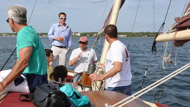 A crew member explains sailing basics to a tour on the Pineapple Ketch.
