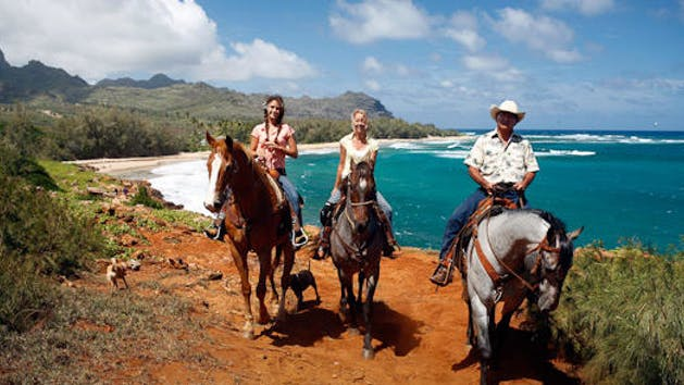 Three people on horseback on Mahaulepu Beach