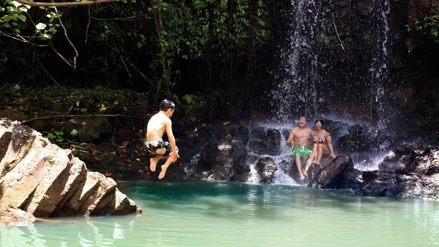 Mountain Waterfall pool in Kauai, a kid doing a cannonball into the water