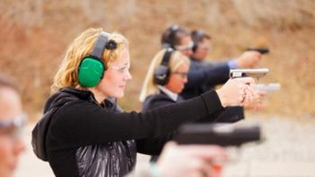 People pointing their pistols at targets at the shooting range