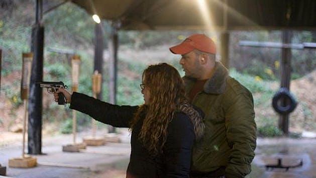 Man watching women point her pistol at target at shooting range