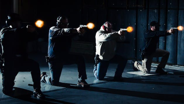 People on one knee firing their pistols in the shooting range with low light