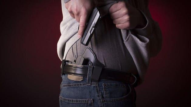 Man putting his pistol into his concealed holster underneath his shirt