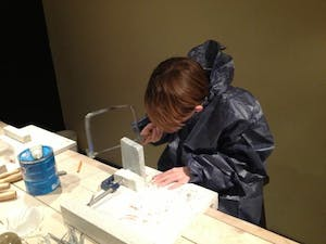 A child learns to carve stone